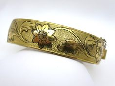 A lovely vintage etched bracelet with floral scrollwork. Victorian in style, it is hinged on one side and has a safety chain.  No marks. There is