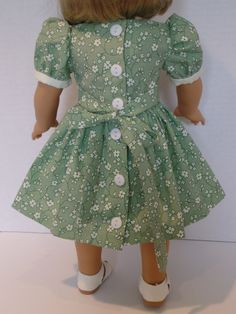 Kit is ready for summer in this dress fashioned from a Keepers Dolly Duds pattern. The 100 percent cotton fabric from Marcus fabrics is light green with cream colored flowers. The bib front is cream cotton fabric edged with ecru colored lace and eight tiny green buttons. The dress has a self tie at the waist that ties in the back. The back closure has six off- white buttons that are sewed over the snaps. All seams are finished or serged. This dress was made in my smoke free home. The do...