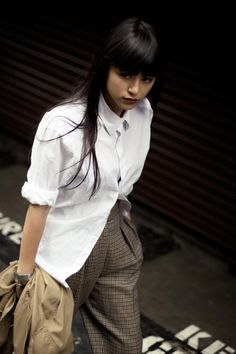 White button-down shirt, plaid trousers -- a totally classic combo. But this lovely lady makes it fresh with the unusual bottoning and high-waisted shape if the trousers. Inspiring.