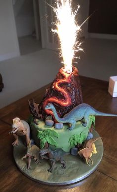 [Homemade] A dinosaur-themed cake I made for my cousins 4th birthday complete with erupting volcano