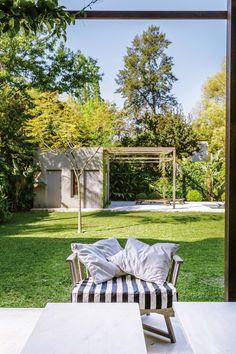 Galería de la casa de María Freytes con mesa baja, sillón individual de madera y almohadones en blanco y estampado a rayas. Detrás, jardín y quincho.