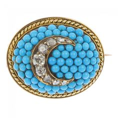 A late Victorian 9ct gold diamond and turquoise brooch, circa 1880. The old and rose-cut diamond crescent, to the circular-shape turquoise cabochon domed panel with rope-twist surround. Estimated total diamond weight 0.40ct. Length 2.6cms. Weight 14.3gms.
