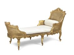 A French late 19th century giltwood daybed in the Louis XV style, with scrolled foliate and rocaille carved frames, on six cabriole legs terminating in scroll feet