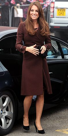 The mom-to-be keeps her belly under wraps in a belted brown coat by Hobbs, which she pairs with black heels and a matching clutch for a stop at the Fishing Heritage Centre in Grimsby, England.