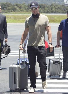Touch down! Chris Hemsworth arrived on the Gold Coast in a tight-fitting T-shirt the day a...