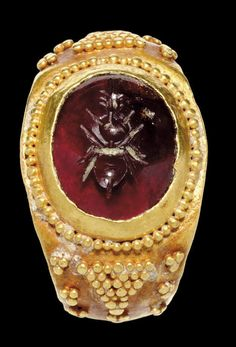 A ROMAN GOLD AND GARNET FINGER RING   CIRCA 2ND CENTURY A.D.   The plain hoop concave on the interior, rounded on the exterior, expanding toward the bezel into rounded shoulders, each embellished with seven clusters of granules around a large triangle of granules, a row of granulation surrounding the oval bezel, set with a convex oval stone engraved with a bee
