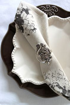 Dark statement plate with white plate a stacked on top, classy napkin and napkin ring.