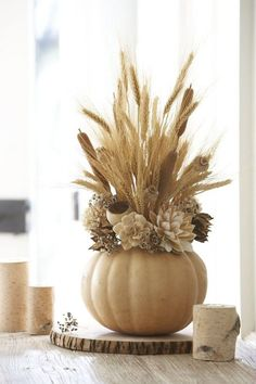 centre de table en épis de blé et fleurs sèches dans un vase en citrouille creusée
