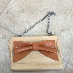 Nanette Lepore leather clutch Super cute clutch with detachable chain strap! Very rarely worn...it has a small water stain on the bow as shown in last photo. Nanette Lepore Bags Clutches & Wristlets