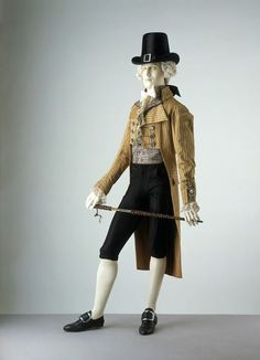 """""""This double-breasted coat demonstrates the exaggerated style of the late 1790s. It has a very high turned-down collar and large revers (lapels). The coat is now cut straight across in front and, following the example of women's dress, the waistline is several inches above the natural level. The double-breasted style in both coats and waistcoats was a fashion that began in the 1780s."""""""