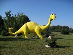 yellow dinosaur in Bear Lake, Michigan; I don't quite understand this, but I think it's cool. Robot Dinosaur, Dinosaur Stuffed Animal, Northern Michigan, Lake Michigan, Road Trip Across America, Plastic Dinosaurs, Roadside Attractions, Prehistoric, Robots