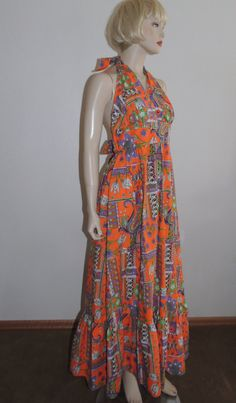 SALE, was $45.00, Fun and Pristine 1970s Backless Halter top Maxi sundress by Mr. B. California. The fabric is washable cotton. The dress has a back zipper, hem ruffle and ties at the back of the neck and at the empire waist in back. No flaws or odors noted. Beautiful orange, white, lavender and electric green flower and paisley design. Please write me if you have questions. Bust: 36 (because of the design 34 to 37) Empire Waist: 30 Length can be modified with the ties at the neckline…