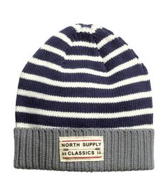 Fine-knit, striped hat in cotton fabric. Contrasting cuff with appliqué at front.