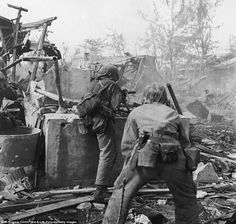 While under fire, U.S. Marines advance on occupying Japanese forces in Tanapag, Saipan in June 1944.