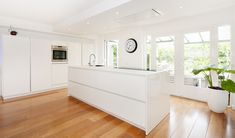 Greeploze hoogglans acryl keuken met glazen werkblad en plafondunit afzuigkap