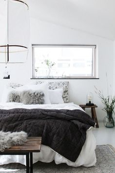 Cozy Scandinavian bedroom with a white lantern above the bed, a cut-out window, gray and white bedding, and a reclaimed wood bench at the foot of the bed