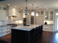 White perimeter cabinets uppers to the ceiling with glass, dark island with light countertop, backsplash polished venatino marble random strips