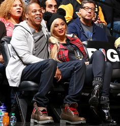 Jay Z and Beyonce (covering her heard with mouse-ear-style hat) at a Nets game