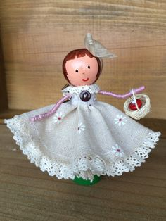 TheFoggyPearCraftCoIsabella peg dolly – standing 11.5cm high..Handmade from a wooden peg, large head bead and stand, this dolly has a handmade dress with petty coat and ruffled knickers and coordinated bow in her hair. She carries a small basket with hand made bead cakes!