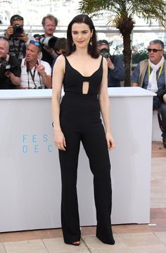 """Weisz is the epitome of chic in her black Narcisco Rodriguez jumpsuit, featuring a nipped waist and horizontal cut-out, at the """"Lobster"""" photocall in Cannes. Her blue and gold earrings are right on trend for this summer's love of tasselled accessories."""