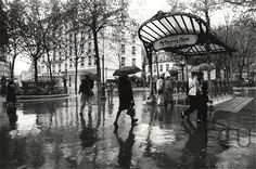 Black and white photo of the metro Place des Abbesses in the rain in the 18th arrondisement, Paris, France