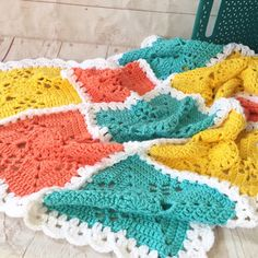 Crochet baby blanket in turquoise, peach, yellow and white