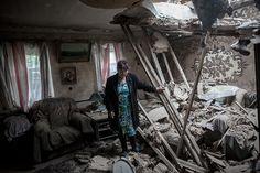 A woman stands in her home destroyed in the Ukrainian troops' shelling of the Golubovka village near Slavyansk on June 27, 2014. (RIA Novosti / Andrey Stenin).