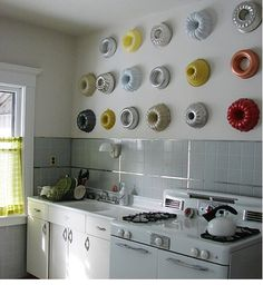 Bundt pans as wall decorations. Not this many, but 3 would look nice, spray painted different colors. They look sort of like wreaths.