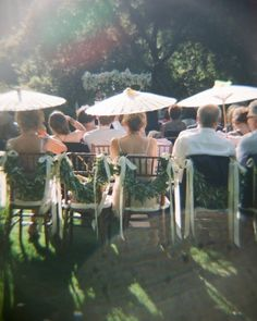 Paper parasols keep guests shaded and cool during an outdoor wedding ceremony