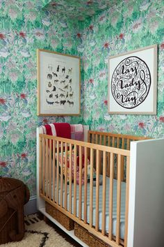 Floral wallpaper covers the walls of a baby's nursery.
