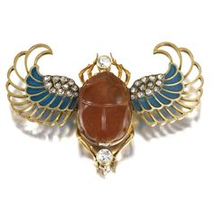 A Russian jewelled and enamelled gold and hardstone brooch, St. Petersburg, 1899-1908, in Egyptian Revival style, the carnelian scarab engraved to the reverse with four horses and a warrior, the wings decorated with plique-à-jour enamel and set with diamonds.