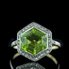A gorgeous and distinctive hexagonal shape, step-cut peridot is framed by a delicate row of rose-cut diamonds. The setting is composed of silver over 18 karat yellow gold with two rose-cut diamonds on each shoulder. A beauty.    Symbolizes happiness; believed to discourage betrayal and to encourage friendship and marriage
