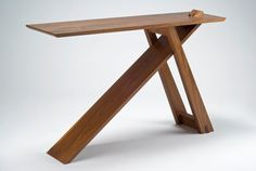 Wedge table: walnut, 30″h x 12″d x 48″l. $2,350. The Wedge table gets at least as much attention as any of my pieces, especially at a show where I often demonstrate how it breaks down easily into three pieces plus the wedge. When setting the table up, the diagonal member first passes through two channels …