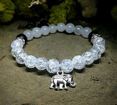 White Crackle / Crystal Balance Elephant Charm Beaded Stretchy Bracelet    New homemade jewelry brand that donates a percent of profits to animal charities or any animal in need of help. Facebook: www.facebook.com/DesignedByNouveau Twitter: @Nouveau Collections Instagram: @NouveauCollections Etsy Shop: www.etsy.com/shop/NouveauYourself
