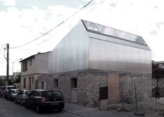 Toulouse architects BAST have renovated a derelict house in the French city by adding a corrugated steel extension that contrasts with the existing masonry.