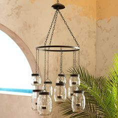 Eight colorful Mason jars are suspended from metal chains for a rustic look that will charm your outdoor hangout. Think front porch, backyard or pool area.
