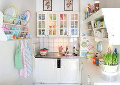 Tiny, white kitchen but they brought in a bunch of color with accessories and with a darker counter top
