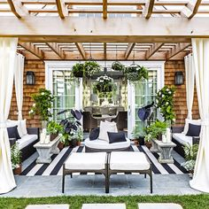 Black and white outdoor space by Caleb Anderson Design. Terrace drapes stripes Frontgate Plants Gardening Hamptons Patio Arbor Pergula