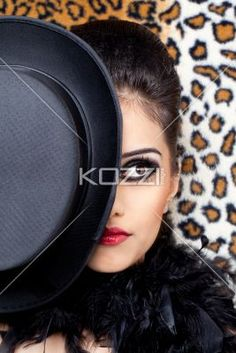 close-up of a confident young woman with a hat. - Close-up of a confident young female fashion model posing with a hat, Model: Kiran Bahugun