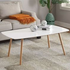 Bring your living room to life with this White Top Mid-Century Coffee Table with Solid Wood Legs. Featuring brilliant white piano finish table tops that are easy to care for and make clean up a breeze