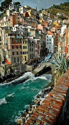 Riomaggiore, Italy ~ the village, dating from the early 13th century, is known for its historic character & its wine, produced by the town's vineyards. Riomaggiore has shoreline on the Mediterranean's Gulf of Genoa, with a small beach & a wharf framed by tower houses. Along with 4 other villages, all connected by trails, it is part of Cinque Terre National Park & is a UNESCO World Heritage Site.