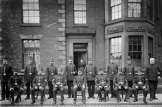 PC John Coupe (front row, seated 2nd from the right) and members of Oldham Borough Police pose for the camera outside their police station in Royton, Oldham. We think this image may date to around 1910. The woman in the doorway is named as Mrs. Jump. www.gmpmuseum.co.uk
