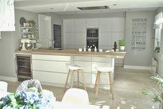 Weiße Küche mit Thekenelement und eine Kastenwand für viel Stauraum