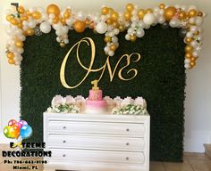 First Birthday party decorations. Irregular balloon arch. Classy and sophisticated. Hedge backdrop and gold ONE sign. Beautifull decorations for this little princess. Party decorations Miami. Balloon decorations.balloon arches. Wedding decorations. Extreme Decorations Ph: 786-663-8198 www.extremedecorations.com extremedecorations@gmail.com