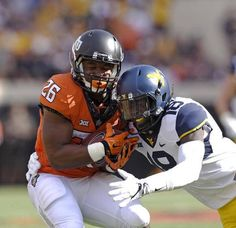 Oklahoma State running back Barry J Sanders (26) works to free himself from the grasp of West Virginia safety Marvin Gross Jr., during the first half of an NCAA college football game in Stillwater, Okla., Saturday, Oct. 29, 2016.