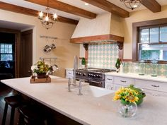 Kitchen: White Granite Countertop In Kitchen With Exposed Beams Ceiling. exposed beams ceiling. classic hood mantel. white countertop. two holes faucet. vintage pendant light. wooden tray. tile backslash. wooden bar stools. green pan.