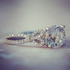 Kirk Kara engagement ring from the Pirouetta collection. Round cut diamond with bow details. Artful, romantic, vintage and  beautiful engagement ring.  Available in Platinum or gold.  Design K174R