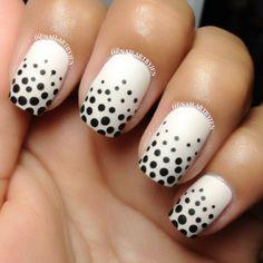 Matte white nails with black polka dots.