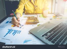 Close up Business woman using calculator and laptop computer for calculating with finance paper.