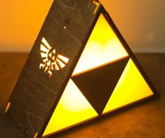 Light up your game room in true Hylian fashion with this Legend Of Zelda Triforce lamp. The Triforce emits a warm yellow glow while the engraved sides of the lamp project the iconic crest of Hyrule onto the nearby walls.